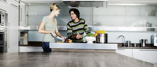 Young couple in modern kitchen, cooking together, smiling
